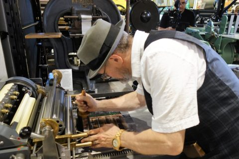 George A. Walker using a proof press to print lines of type from the Linotype machine