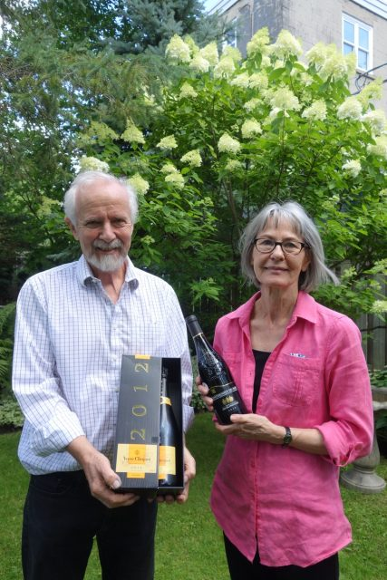 Tim and Elke Inkster holding celebratory bottles of libations.